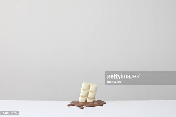 Conceptual bar of white chocolate in a pool of melted milk chocolate