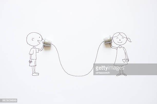 Conceptual boy and girl talking with tin can phones