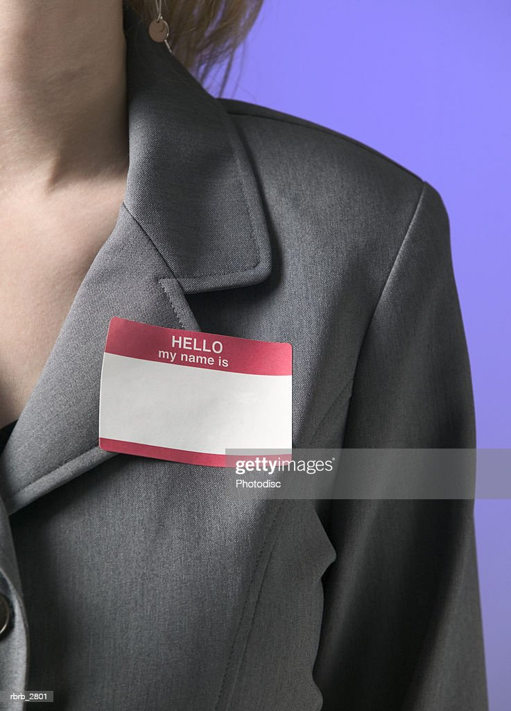 conceptual business shot of a female in a grey suit with a blank name tag : Foto de stock