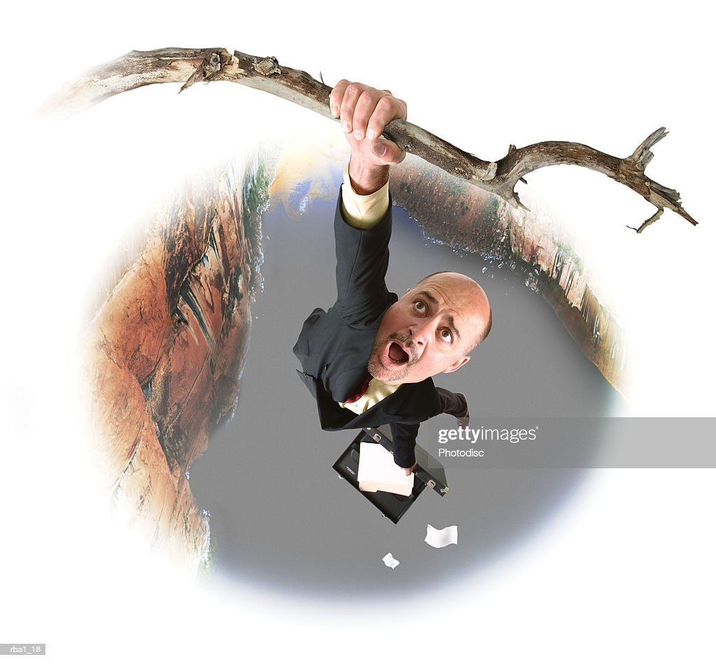 conceptual caricature of a caucasian business man in a suit as he hangs from a branch over a large canyon : Stockfoto
