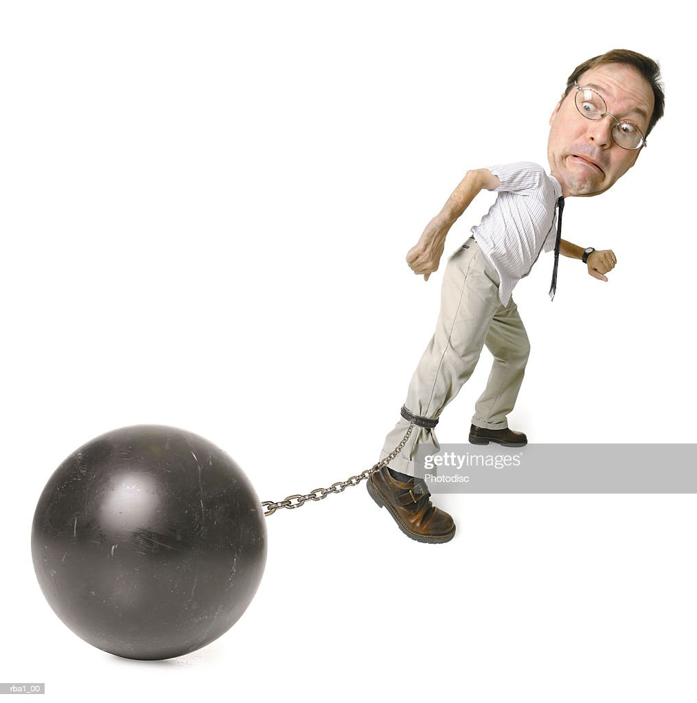 conceptual caricature of a caucasian man in a shirt and tie as he drags a big ball and chain around : Stock Photo