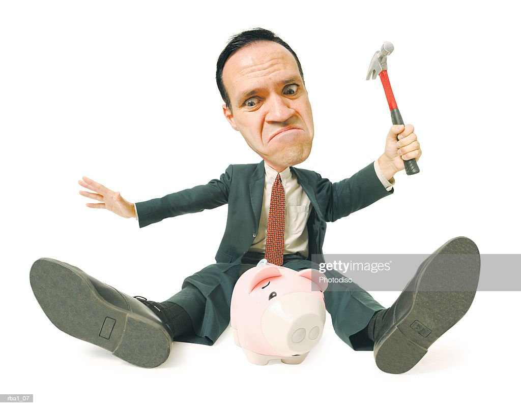 conceptual caricature of a caucasian man in a suit as he attempts to smash a piggy bank with a hammer : Stockfoto