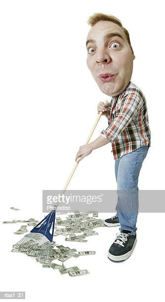 conceptual caricature of a caucasian man in a work clothes as he rakes up money as if they were leaves - jardinier humour photos et images de collection