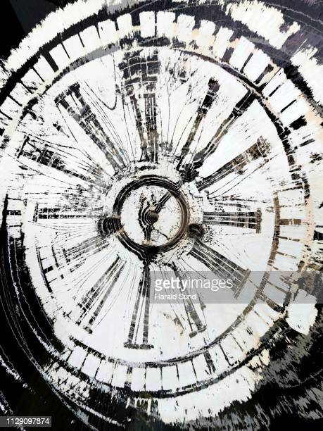 Conceptual, close-up, distorted, distressed appearing vintage antique grandfather clock face with Roman numeral numbers and hour and second hands.