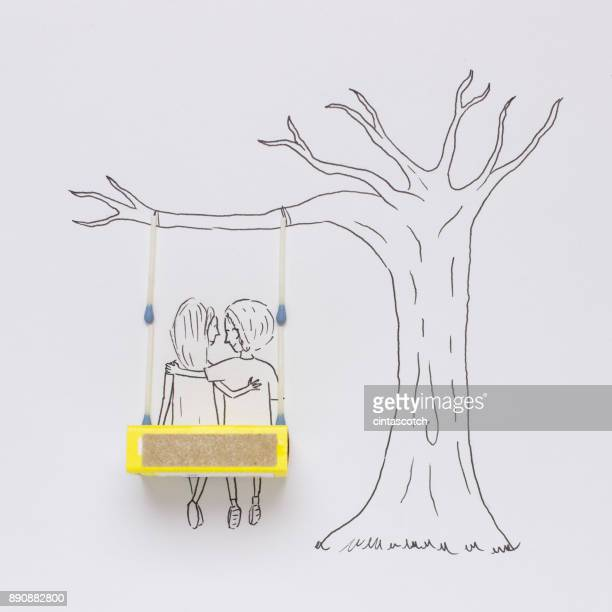 Conceptual couple sitting on a swing together