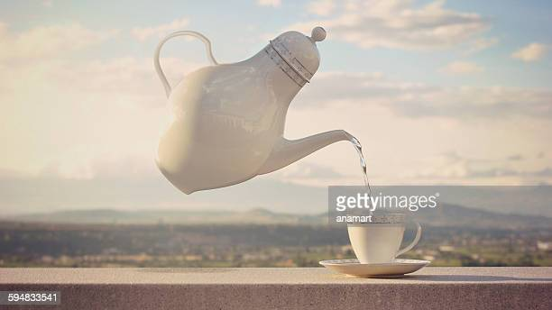 Conceptual floating teapot pouring tea into a cup