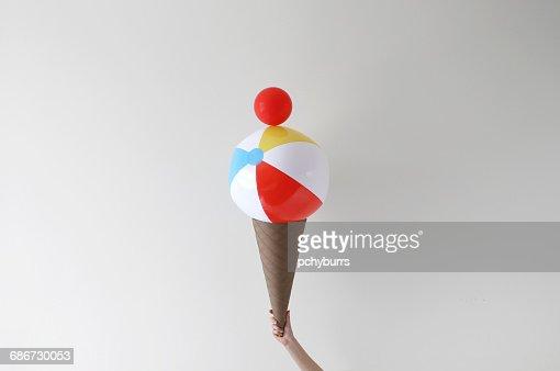 Conceptual Hand holding giant ice-cream cone