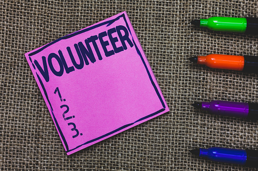Conceptual hand writing showing Volunteer. Business photo showcasing Person who freely offers to take part in something Charity Purple Paper Important reminder Markers Jute background. 1056068310
