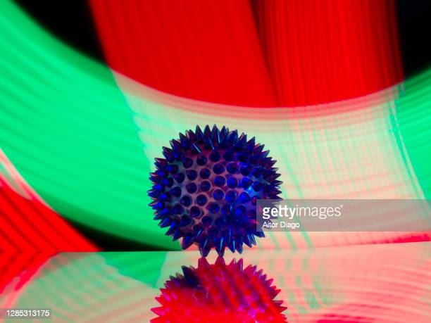 conceptual image of a coronavirus in a colourful background. - disease vector stock pictures, royalty-free photos & images
