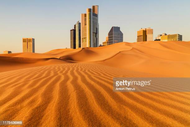 conceptual image of a metropolis with skyscrapers in the desert - doha stockfoto's en -beelden