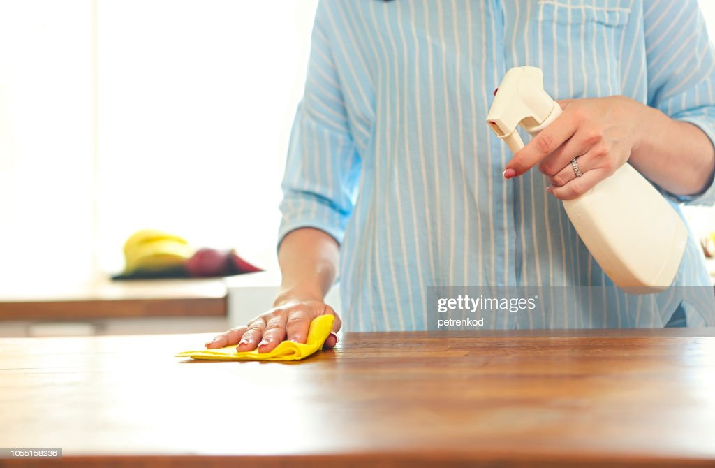 Conceptual image of kitchen cleaning. Close up of human handholding spray bottle with cleaning liquid : Stock Photo