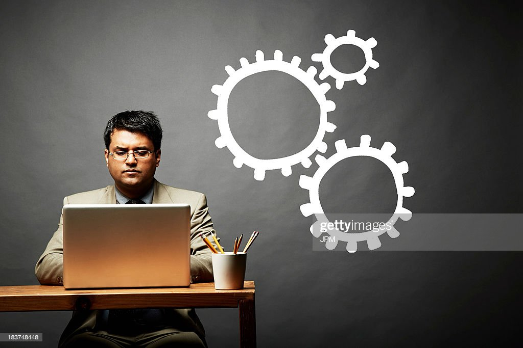 Conceptual image of man as cog in the wheel : Stock Photo
