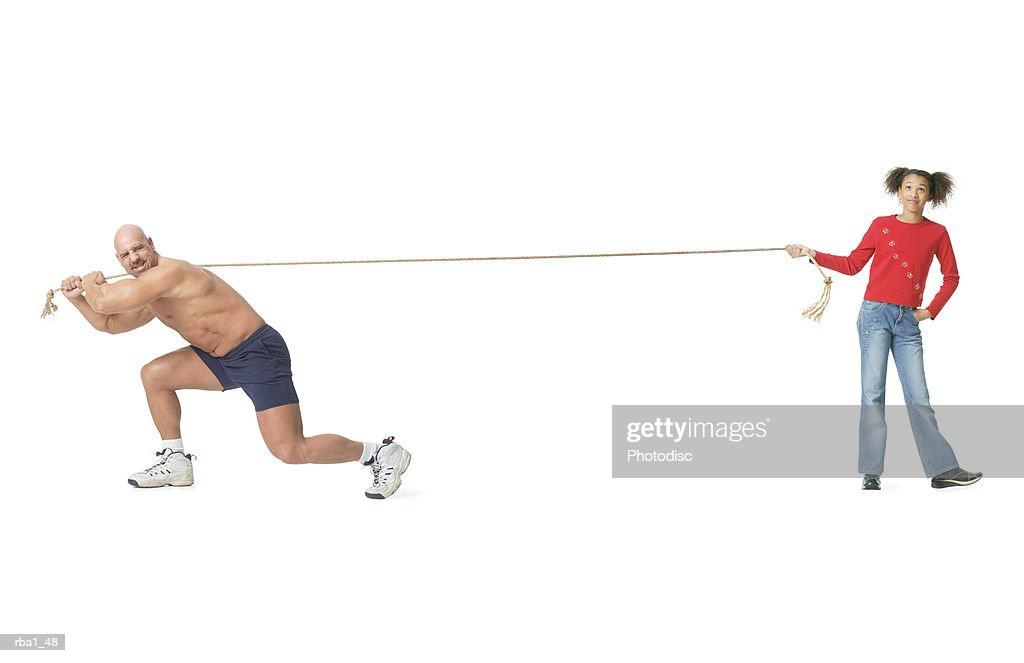 conceptual of caucasian male weightlifter he loses a tug of war with a little african american girl : Stockfoto