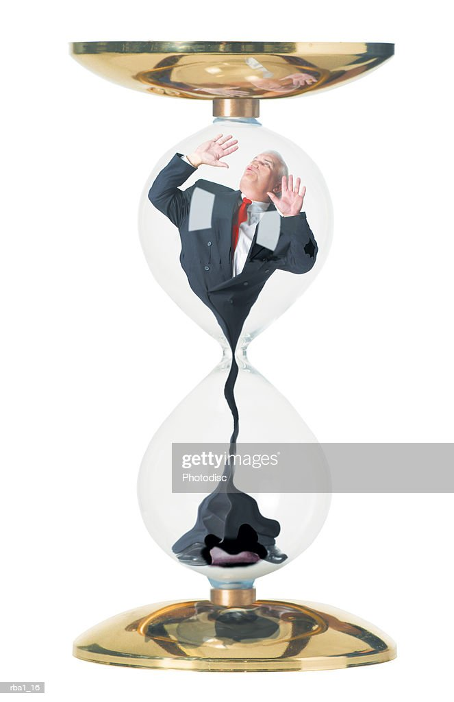 conceptual photo of a caucasian business man in a suit as he is stuck in and sucked through an hourglass : Stockfoto