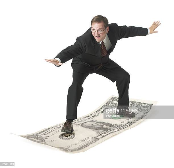 conceptual photo of a caucasian business man in a suit as he playfully surfs on a dollar bill