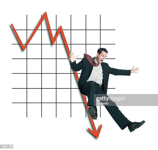 conceptual photo of a caucasian man in a suit as he slides down a plummeting line on a graph