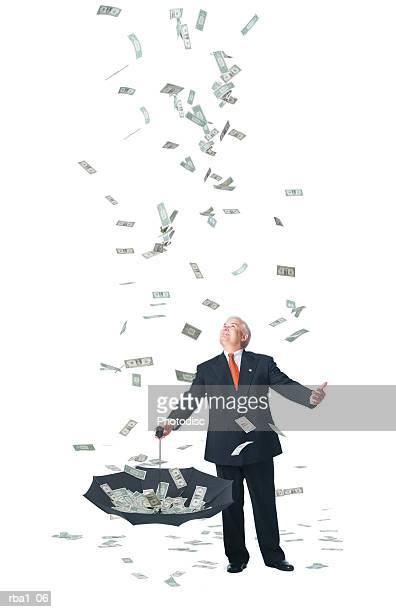 conceptual photo of a caucasian man in a suit standing in raining money and catches it in umbrella
