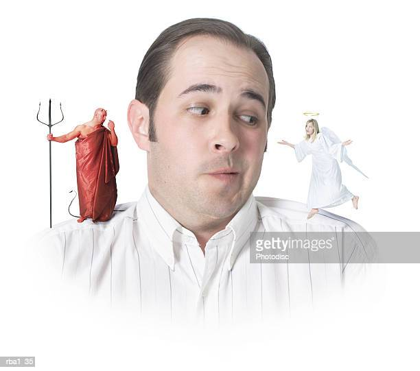 conceptual photo of a caucasian man with an angel and a devil on his shoulders as he confusedly glances to the angel