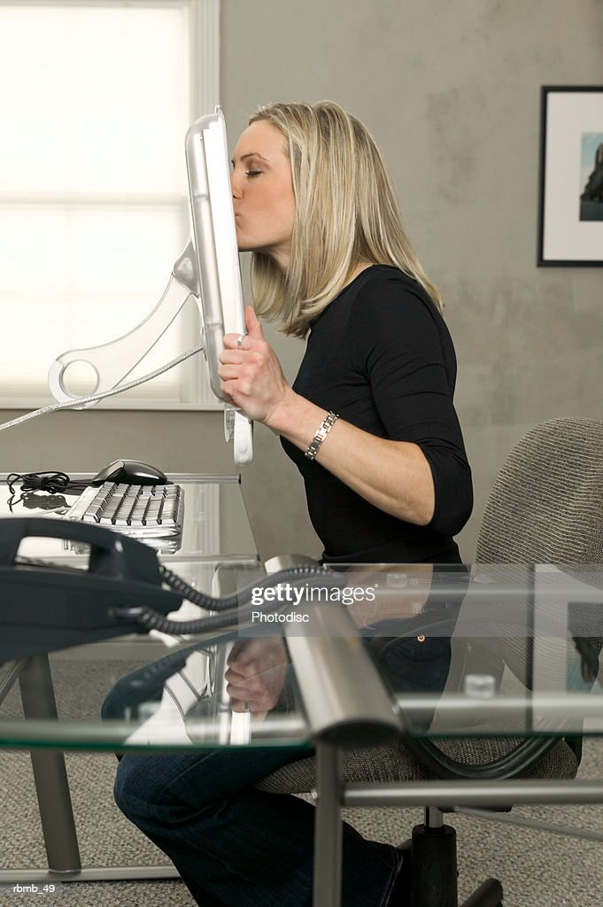 conceptual photo of a young blonde woman as she holds up the computer screen and kisses it : Stockfoto