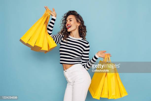 conceptual photo of happy girl holds shopping packages on blue background - yellow trousers stock pictures, royalty-free photos & images