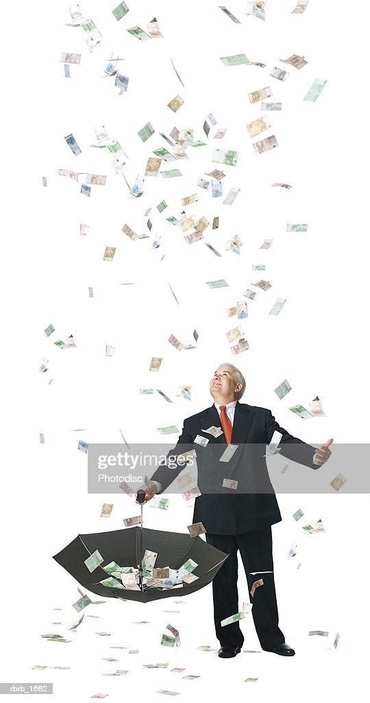 conceptual photograph of a business man as he catches raining euros in his umbrella : Stockfoto