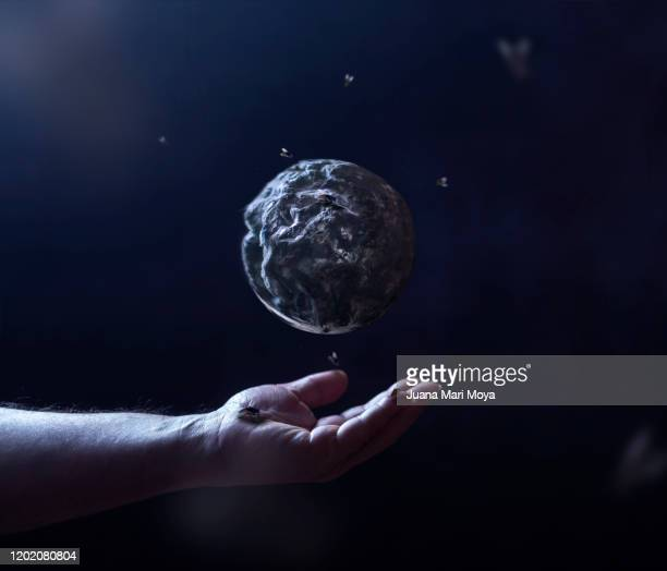 conceptual photograph of man's hand, which dominates and rots the planet earth - world at your fingertips stock pictures, royalty-free photos & images