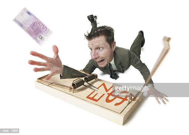 conceptual photogrpah of a business man stuck in a mouse trap as he reaches for an euro