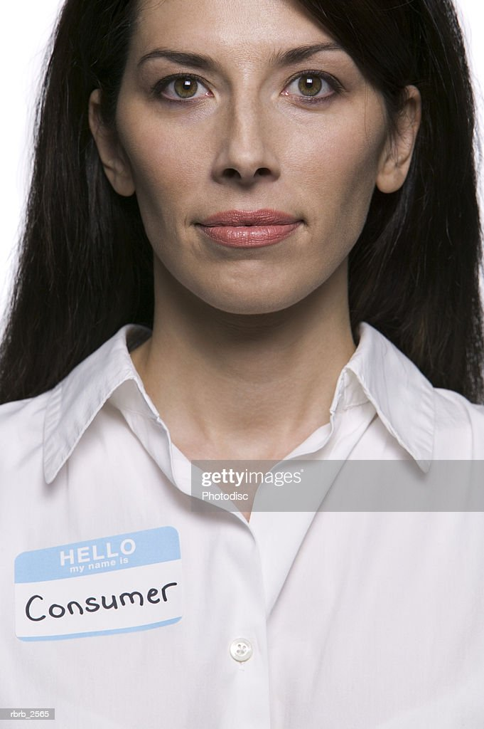 conceptual portrait of an adult brunette woman wearing a name tag stating she is a consumer : Foto de stock