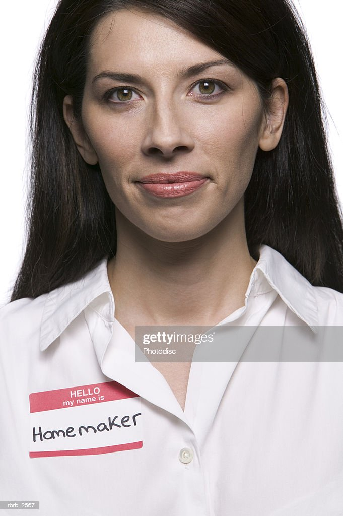 conceptual portrait of an adult brunette woman wearing a name tag stating she is a homemaker : Foto de stock
