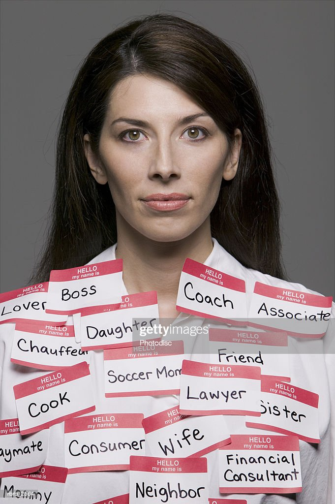conceptual portrait of an adult brunette woman who is covered with multiple labels and name tags : Foto de stock