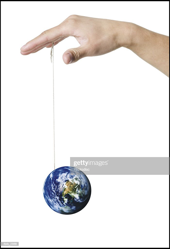 conceptual shot of a hand playing with an earth yo yo dangling on a string : Foto de stock