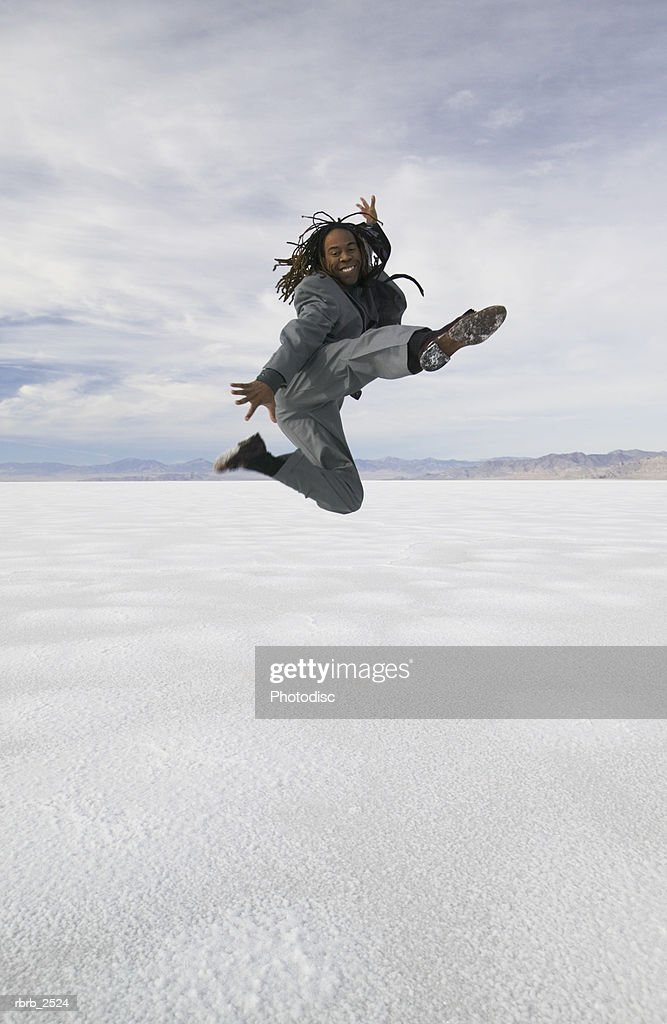 conceptual shot of a young adult business man in a grey suit as he jumps and kicks through the air in a desert : Foto de stock
