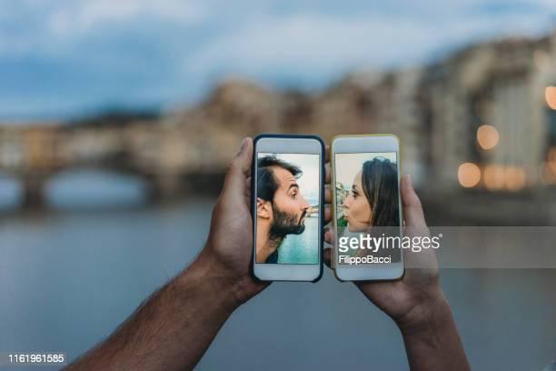 konzeptaufnahme eines jungen erwachsenen paares, das sich per handy küsst - freundschaftliche verbundenheit stock-fotos und bilder