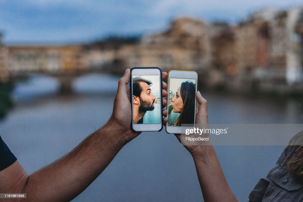 Conceptual shot of a young adult couple kissing via mobile phone : Stock Photo