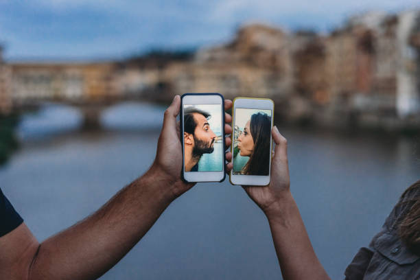 conceptual shot of a young adult couple kissing via mobile phone - couples romance stock pictures, royalty-free photos & images