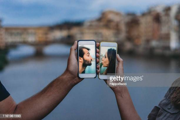 conceptual shot of a young adult couple kissing via mobile phone - romance stock pictures, royalty-free photos & images