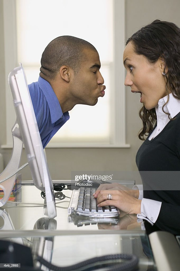 conceptual shot of a young adult female met by a kissing man coming out of her computer screen : Foto de stock
