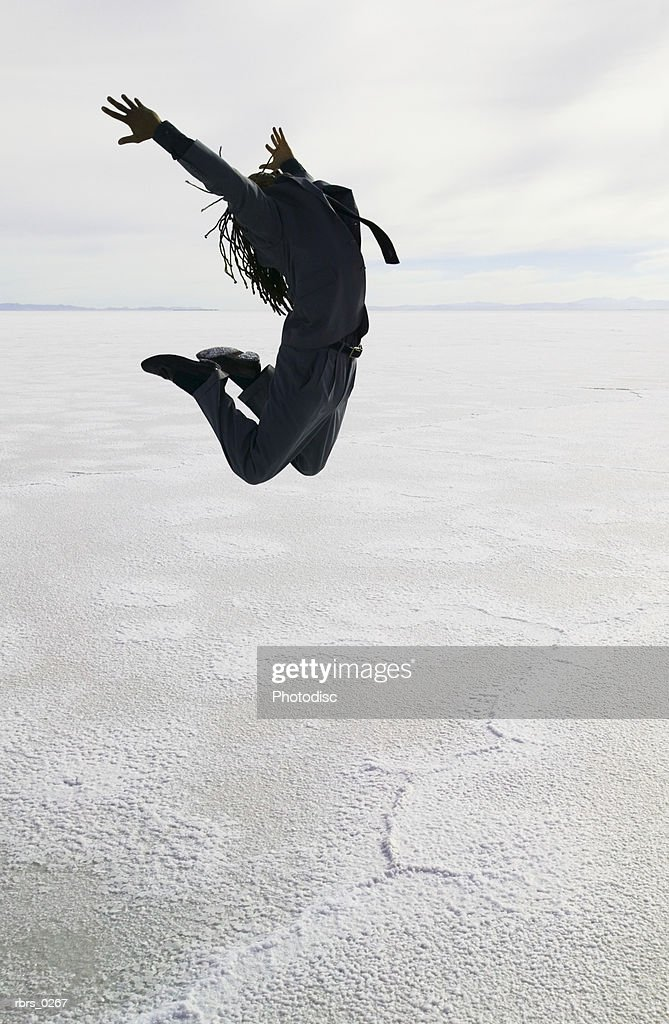 conceptual shot of a young adult male as he jumps through the air in the middle of a desert : Stock Photo