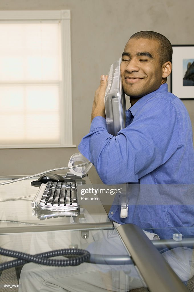 conceptual shot of a young adult male as he lovingly hugs his computer screen : Foto de stock