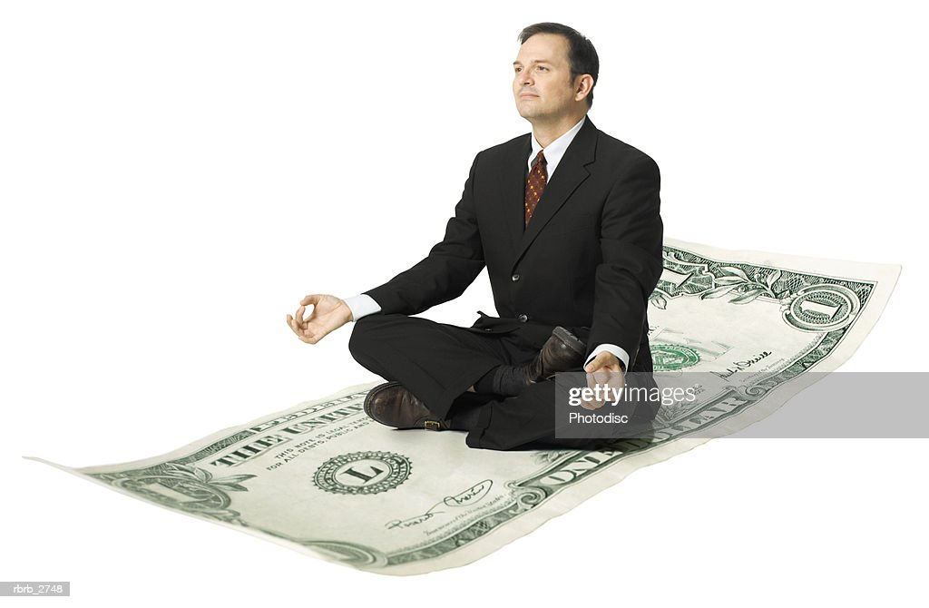 conceptual shot of an adult business man in a suit as he mediates atop a dollar bill : Foto de stock
