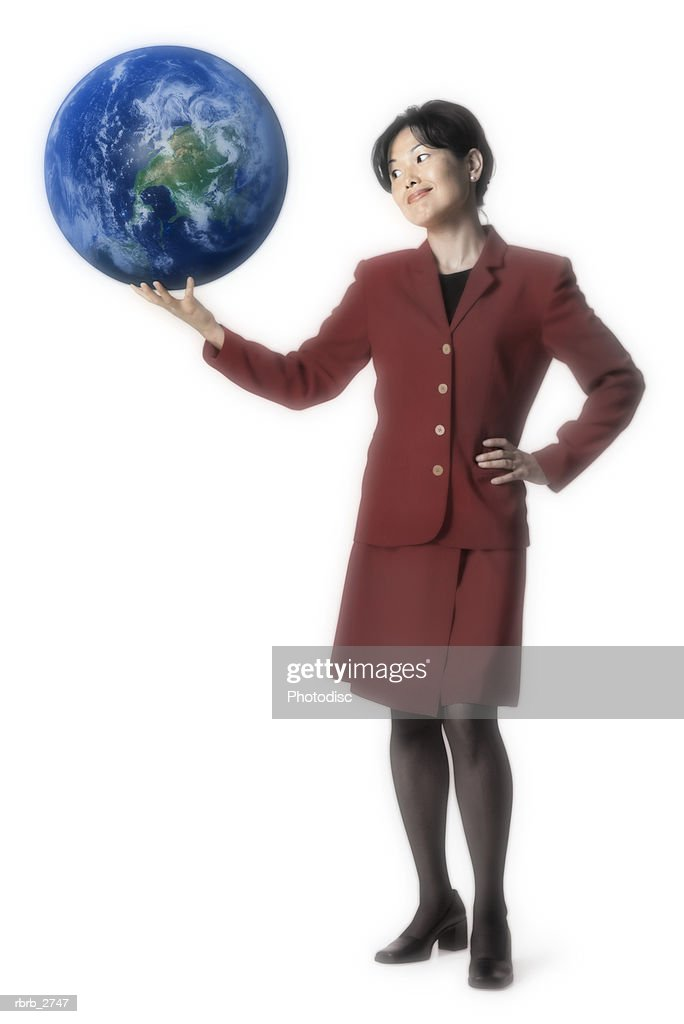 conceptual shot of an adult business woman in a red dress as she holds up the whole world : Foto de stock