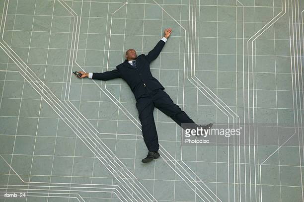 conceptual shot of an african american business man as he lays flat on the ground holding his phone - fainting stock pictures, royalty-free photos & images