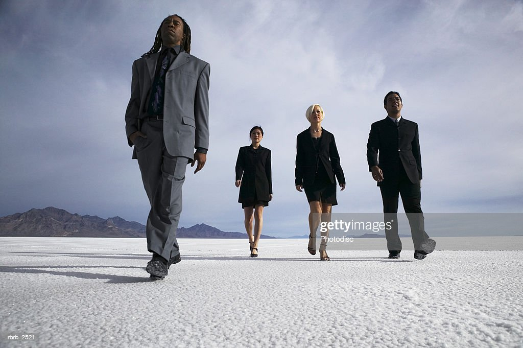 conceptual shot of four business people as they confidently walk through an open desert : Foto de stock