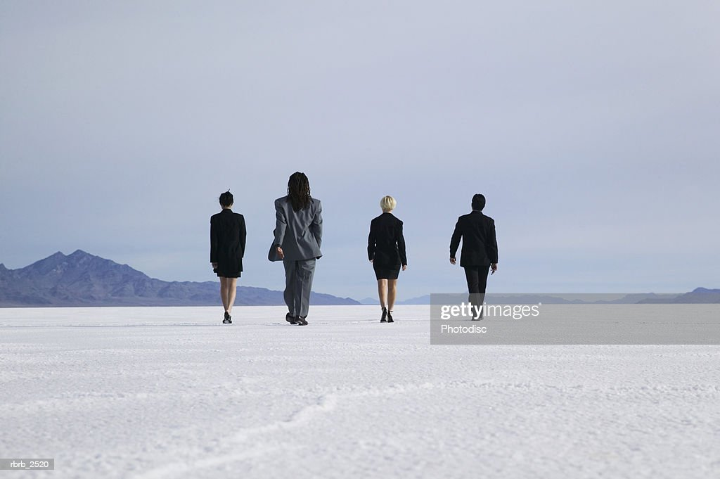conceptual shot of four business people as they walk together through an open desert : Foto de stock