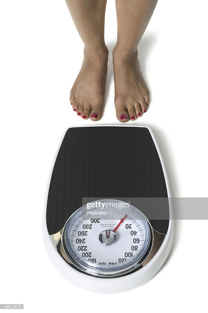 conceptual shot of the feet of a young adult woman as she in about to step on the scale : Foto de stock