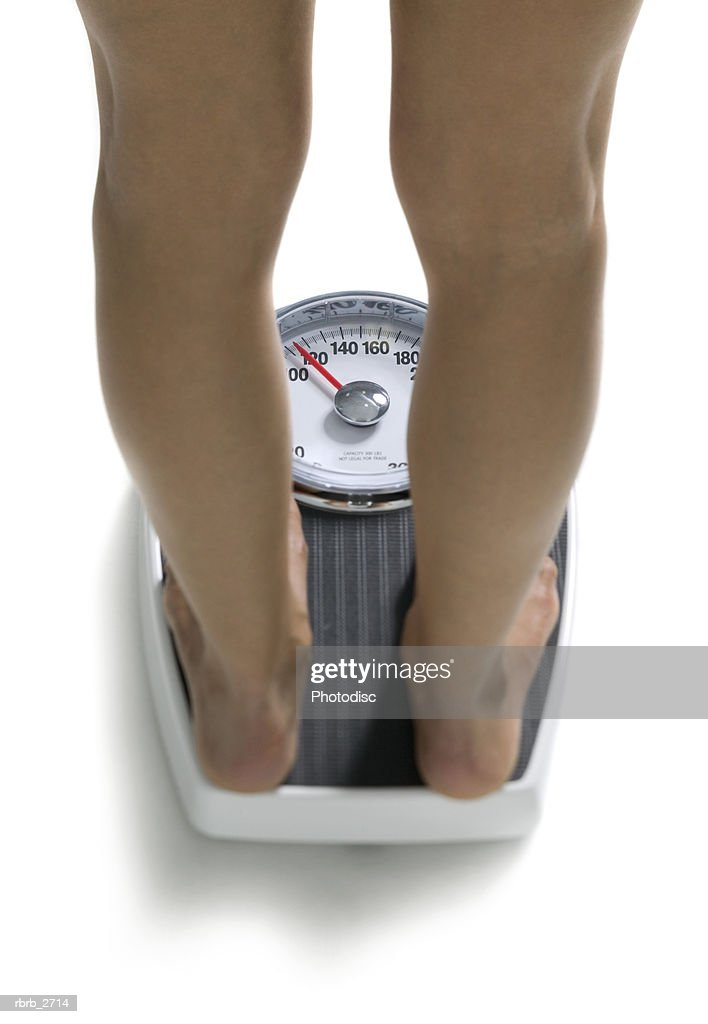 conceptual shot of the legs of a young adult woman as she stands on a bathroom scale : Foto de stock