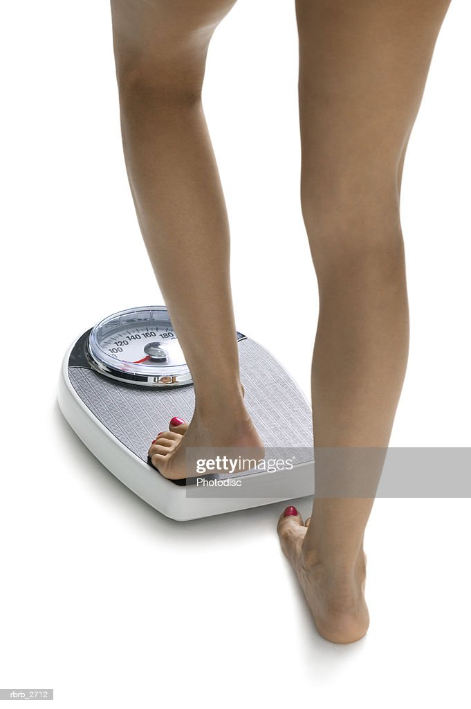 conceptual shot of the legs of a young adult woman as she steps on a bathroom scale : Foto de stock