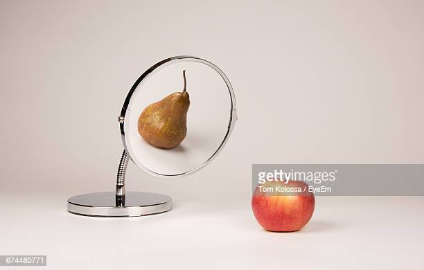 Conceptual Still Life With Two Fruits And A Mirror