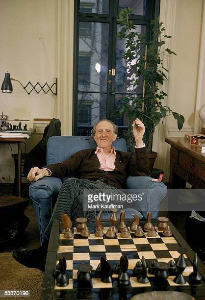 Conceptual surrealist artist Marcell Duchamp relaxing in his apartment behind a chessboard with pieces designed by fellow artist Max Ernst.