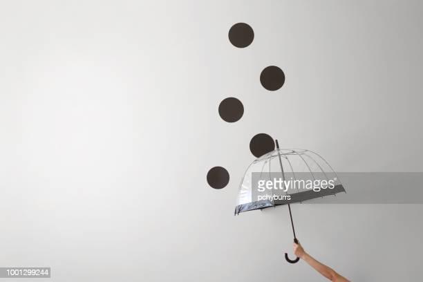 conceptual woman holding an umbrella in the rain - 傘 ストックフォトと画像